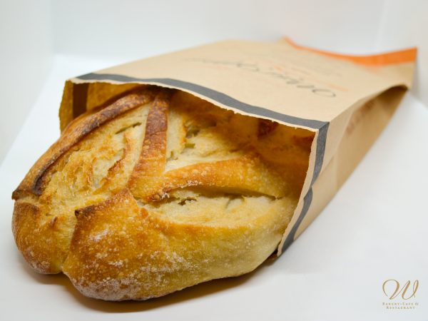 Wild Wheat Pain Au Levain in a paper bag