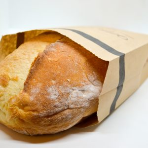 Loaf of Wild Wheat Swiss Peasant bread in a paper bag